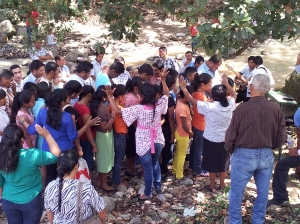 The new believers being prayed over before being baptized.